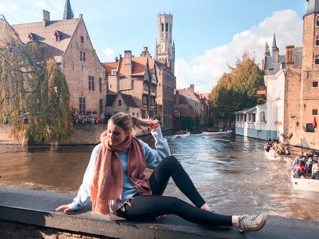 Girl sitting on a wall in front of the main canal of Bruges.